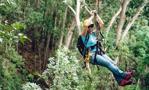 woman ziplining in hawaii and sticking her tongue out